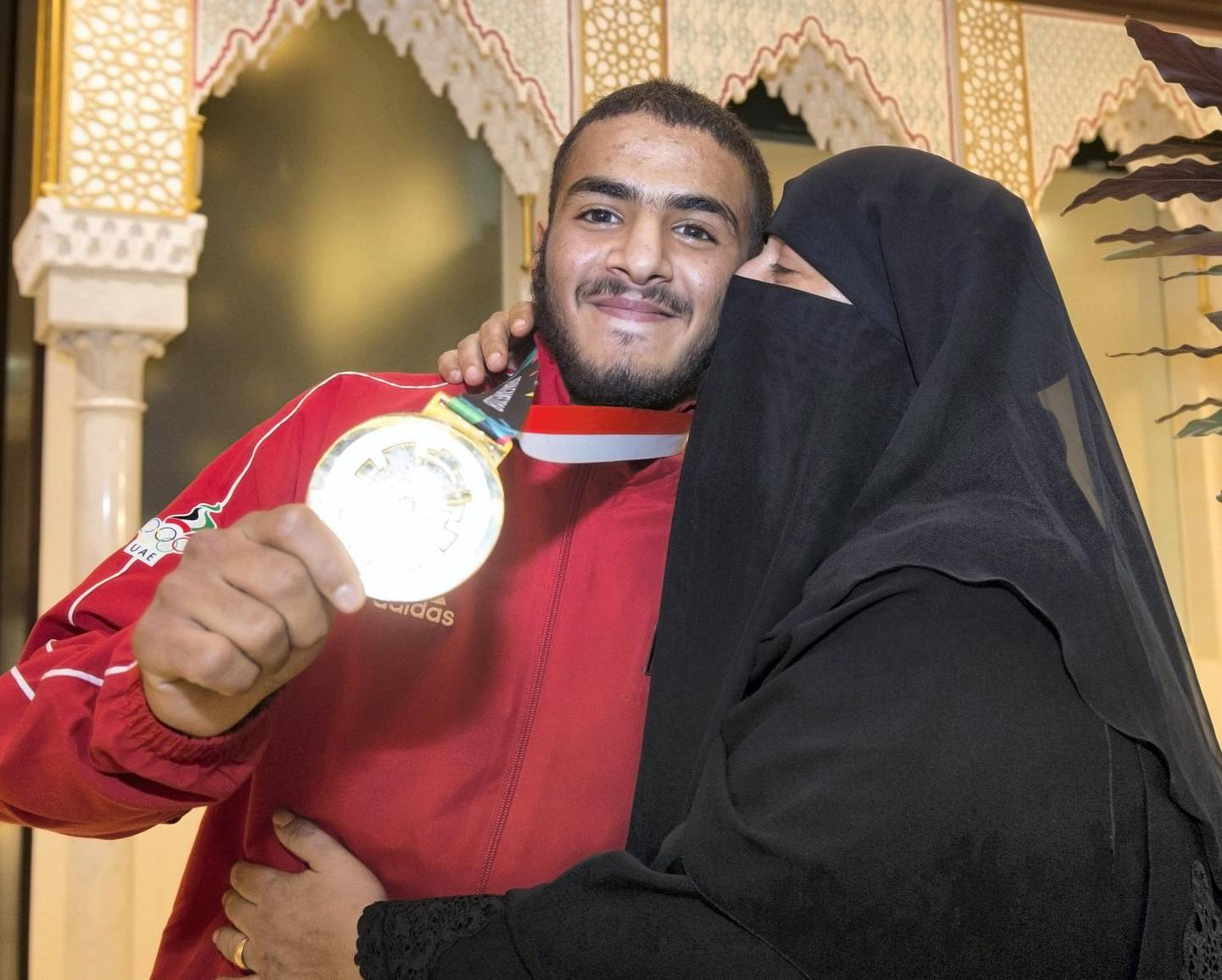 ABU DHABI, UNITED ARAB EMIRATES  27 August 2018- Hamad Nawad gold medalist 56kg division with his mother giving him a kiss at the welcome celebration for the UAE National Jiu-Jitsu team from the Asian Games (ASIAD) in Jakarta, Indonesia. The team gathered  total of 9 medals in various weight categories at Abu Dhabi International Airport VIP terminal, 27 August 2018.  Leslie Pableo for The National for Anna Zackarias story