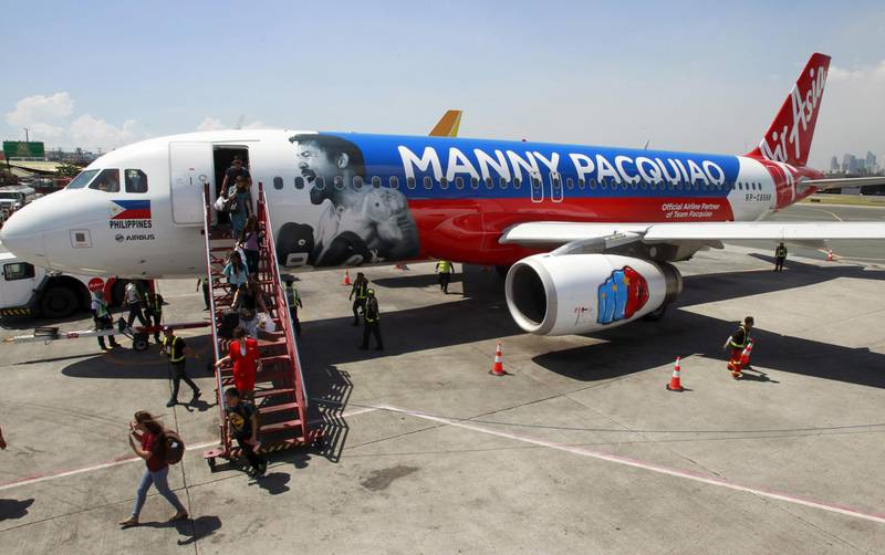 Passengers disembark the AirAsia Philippines Airbus A320 plastered with the image of Filipino boxer Manny Pacquiao as they arrive from Cebu at the domestic airport in Pasay city, metro Manila Apiril 28, 2015. AirAsia Philippines show their support to Pacquiao by painting their aircraft with the boxing icon's name and face, an AirAsia official said. Pacquiao is set to fight American boxer Floyd Mayweather Jr. on May 2 at Las Vegas, Nevada.     REUTERS/Romeo Ranoco