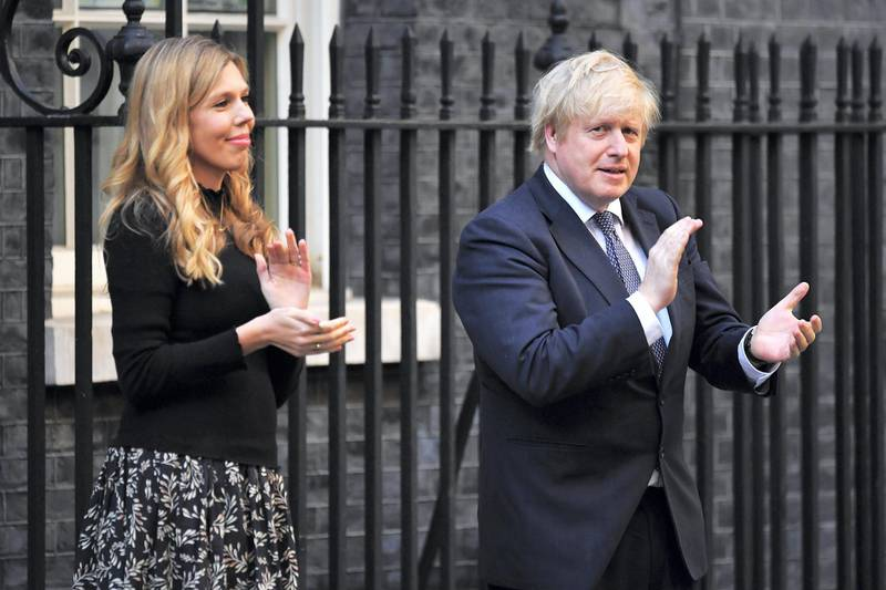 """LONDON, ENGLAND - MAY 14:  Prime Minister Boris Johnson and his fiancée Carrie Symonds applaud for key workers outside 10 Downing Street on May 14, 2020 in London, England. Following the success of the """"Clap for Our Carers"""" campaign, members of the public are being encouraged to applaud NHS staff and other key workers from their homes at 8pm every Thursday. The Coronavirus (COVID-19) pandemic has infected over 4 million people across the world, claiming at least  33,614 lives in the U.K. (Photo by Leon Neal/Getty Images)"""