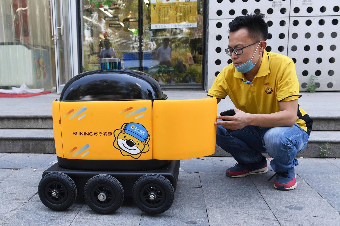 """In this photo taken on June 28, 2018, a Suning worker loads a delivery robot with groceries outside a Suning supermarket during a demonstration of the robot in Beijing. Along a quiet residential street on the outer edges of Beijing, a yellow and black cube about the size of a small washing machine trundles leisurely to its destination. This """"little yellow horse"""" is an autonomous delivery robot, ferrying daily essentials like drinks, fruit and snacks from the local store to the residents of the """"Kafka"""" compound in the Chinese capital.  - TO GO WITH AFP STORY CHINA-TECHNOLOGY-ROBOTS-CONSUMER-SCIENCE,FEATURE BY LUDOVIC EHRET  / AFP / GREG BAKER / TO GO WITH AFP STORY CHINA-TECHNOLOGY-ROBOTS-CONSUMER-SCIENCE,FEATURE BY LUDOVIC EHRET"""