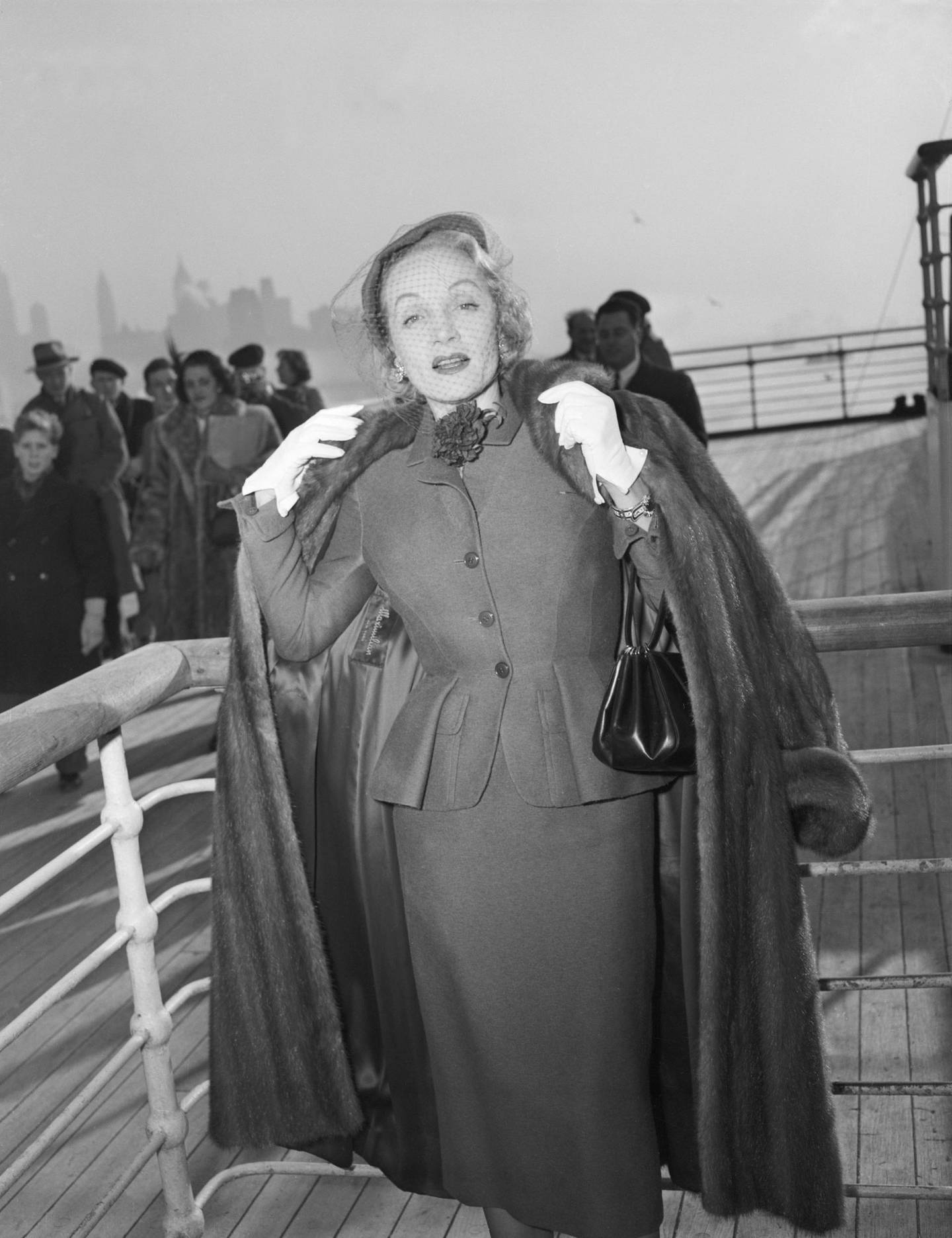 (Original Caption) 12/21/1950-New York, New York- Actress, Marlene Dietrich, unquestionably one of the most glamourous grandmothers in the world, shows herself to be little the worse for wear after her arrival at New York aboard the Queen Elizabeth. Getty ImagesMarlene Dietrich wearing day suit by Christian Dior onboard the Queen Elizabeth arriving in New York, 21 December 1950. Getty Images