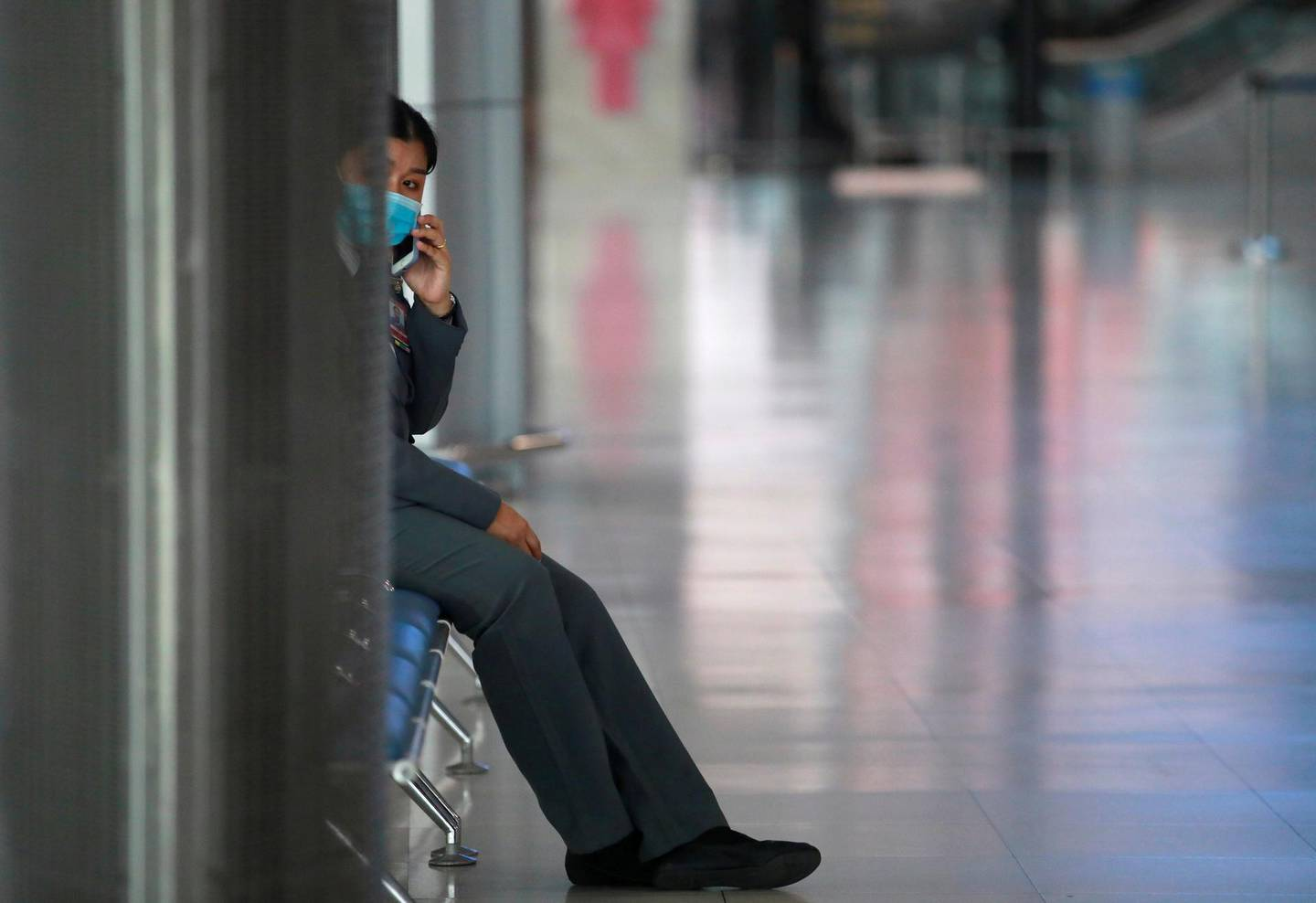 A staff wearing a protective face mask uses her phone at Suvarnabhumi Airport as the government extends a ban on incoming passenger flights until the end of April, following the coronavirus disease (COVID-19) outbreak, in Bangkok, Thailand April 16, 2020. REUTERS/Soe Zeya Tun