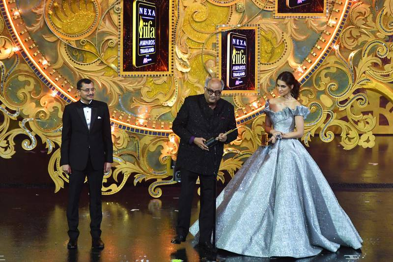 """Bollywood film producer Boney Kapoor (C) receives the award for best performance in a leading role - female in behalf of his late wife and actress Sridevi for her role in """"Mom"""" while Bollywood actress Kriti Sanon (R) and Tarun Garg (L) executive director Maruti Suzuki and executive vice president of Nexa looks on during the IIFA Awards of the 19th International Indian Film Academy (IIFA) festival at the Siam Niramit Theatre in Bangkok on June 24, 2018. / AFP / INDRANIL MUKHERJEE"""
