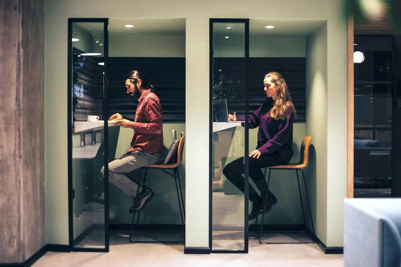 A woman and a man studying.  The reality of social distancing affects the interior architectural designs of workspaces and academic areas.