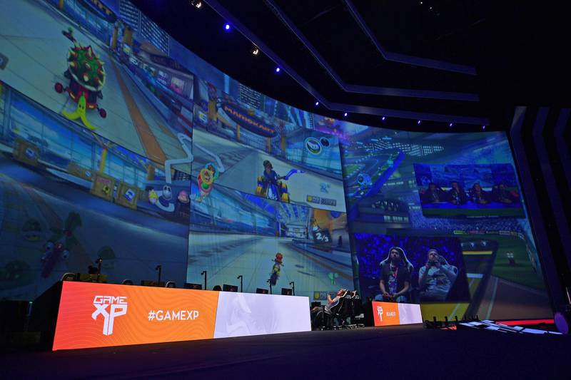 Gamers play Mario Kart on a giant video screen during the Game XP event at the Olympic Park in Rio de Janeiro, Brazil on September 7, 2018. - The four day event aims to be the largest video gaming event in Latin America and attracts computer gamers and comic book enthusiasts. (Photo by CARL DE SOUZA / AFP)