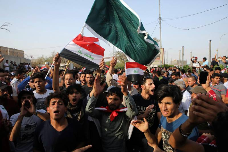 Iraqi protesters wave national flags in front of the provincial council building during a demonstration demanding better public services and jobs, in Basra, 340 miles (550 km) southeast of Baghdad, Iraq, Friday, July 27, 2018. (AP Photo/Nabil al-Jurani)