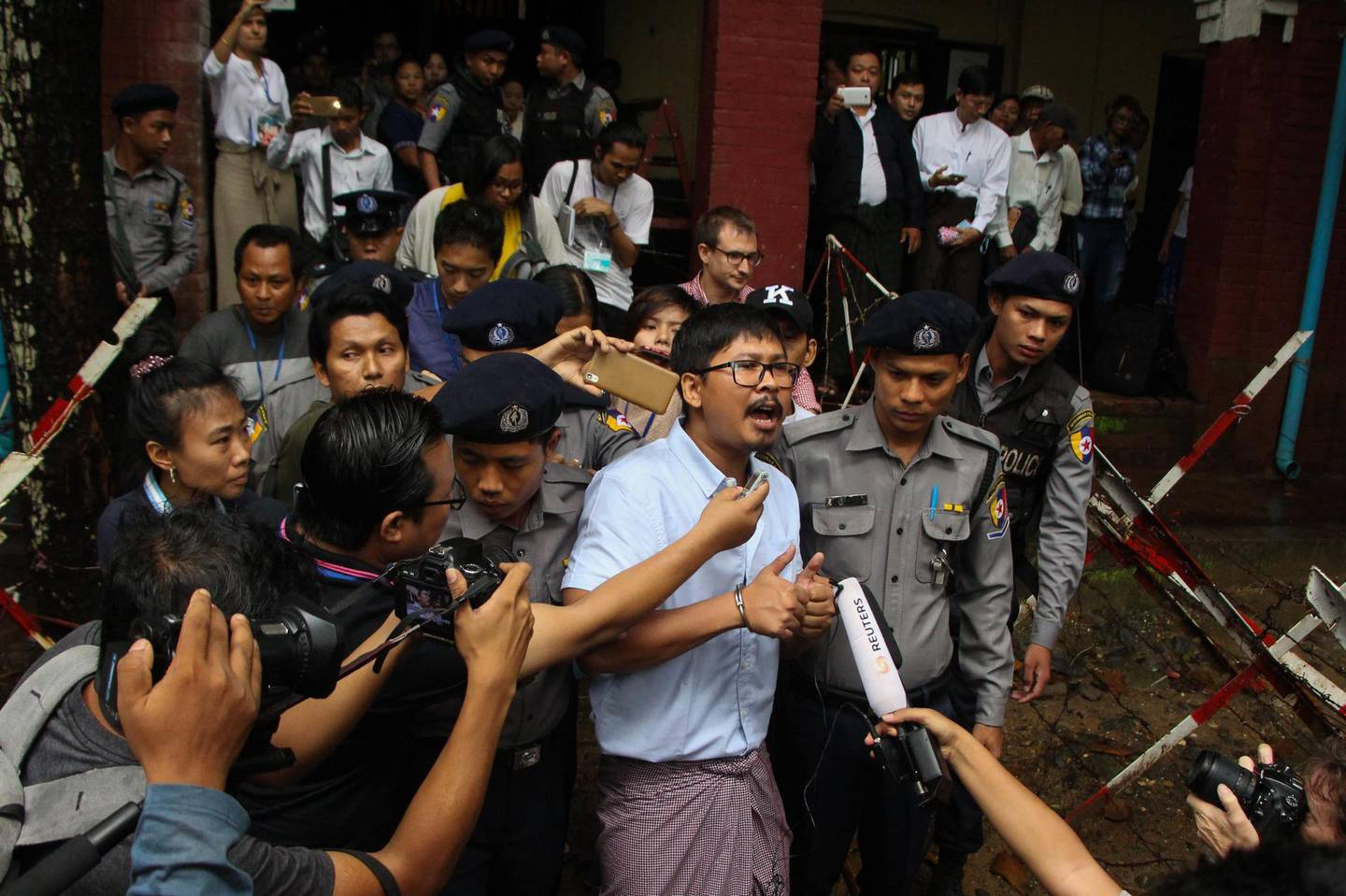 Detained Myanmar journalist Wa Lone (C) speaks to reporters while escorted by police to a court for his ongoing pre-trial hearing in Yangon on July 9, 2018. Two Reuters reporters accused of breaking Myanmar's draconian secrecy law during their reporting of the Rohingya crisis must face trial, a judge ruled on July 9, on a charge that carries up to 14 years in jail. / AFP / STR