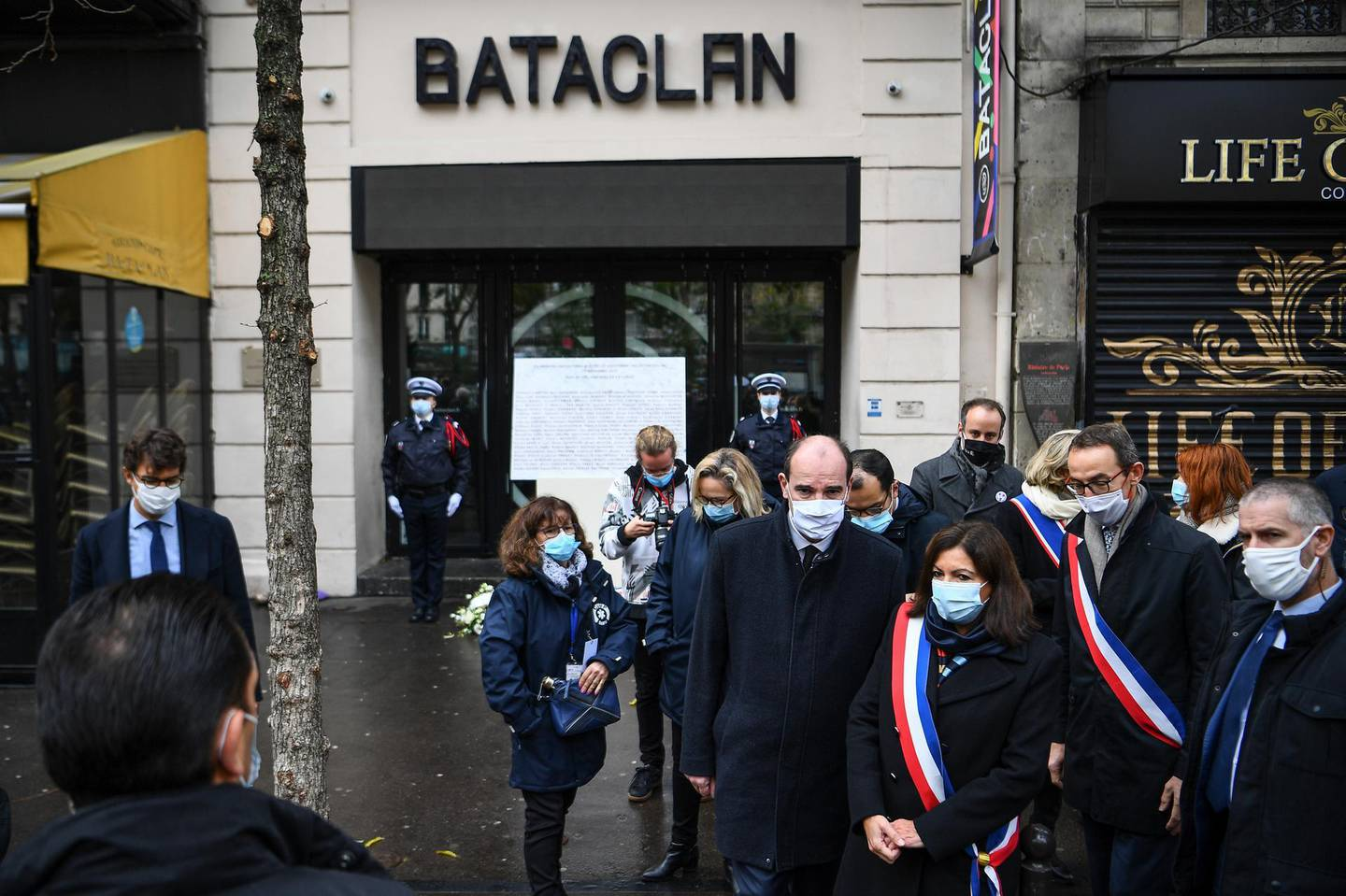 French Prime Minister Jean Castex, center, and Paris Mayor Anne Hidalgo, 3rd right, participate in a wreath laying ceremony, marking the 5th anniversary of the Nov. 13, 2015 attacks outside the Bataclan concert hall in Paris, Friday, Nov. 13, 2020. In silence and mourning, France is marking five years since 130 people were killed by Islamic State extremists who targeted the Bataclan concert hall, Paris cafes and the national stadium. (Christophe Archambault/Pool Photo via AP)
