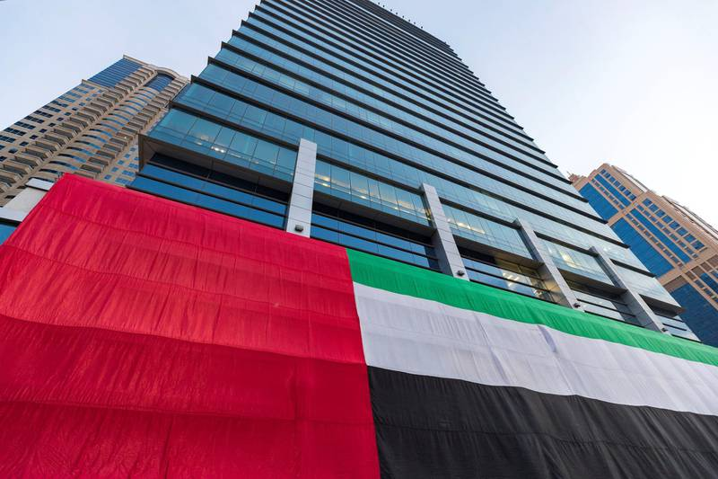 Dubai, United Arab Emirates - November 27, 2018: A giant flag is displayed on a skyscraper in JLT for National day. Tuesday the 27th of November 2018 in JLT, Dubai. Chris Whiteoak / The National