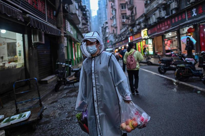 A person wearing a face mask as a preventive measure against the spread of the COVID-19 novel coronavirus carries groceries in a neighbourhood in Wuhan in China's central Hubei province on April 20, 2020. A bride in a white gown poses by Wuhan's East Lake while a grandfather swings his tiny grandson in a hammock strung between trees, and families enjoy a picnic on a sunny afternoon: Wuhan is returning to normal after enduring a 76-day quarantine. - TO GO WITH Health-virus-China-Wuhan,FOCUS by Jing Xuan Teng  / AFP / Hector RETAMAL / TO GO WITH Health-virus-China-Wuhan,FOCUS by Jing Xuan Teng