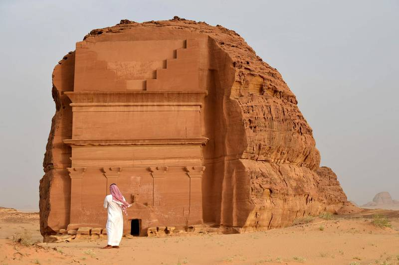 (FILES) This file photo taken on March 31, 2018 shows a man standing outside of the Qasr al-Farid tomb (The Lonely Castle) carved into rose-coloured sandstone in Madain Saleh, a UNESCO World Heritage site, near Saudi Arabia's northwestern town of al-Ula. Citizens from 49 countries are now eligible for tourist visas online or on arrival to Saudi Arabia, thanks to a landmark decision enacted last month, relaxing rules that had largely restricted visits to business travellers and Muslim pilgrims, with the authorities banking on large cities like the capital Riyadh and the western Red Sea port of Jeddah through large-scale investments, including in entertainment.  / AFP / FAYEZ NURELDINE