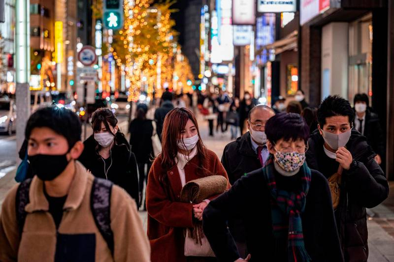 People walk on a shopping area on Christmas eve, in Ginza district of Tokyo on December 24, 2020. / AFP / Philip FONG