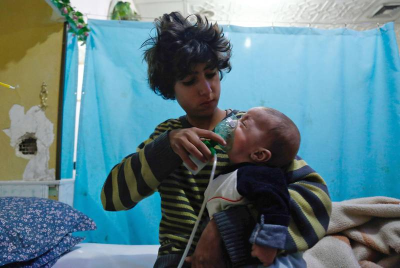 TOPSHOT - A Syrian boy holds an oxygen mask over the face of an infant at a make-shift hospital following a reported gas attack on the rebel-held besieged town of Douma in the eastern Ghouta region on the outskirts of the capital Damascus on January 22, 2018.  At least 21 cases of suffocation, including children, were reported in Syria in a town in eastern Ghouta, a beleaguered rebel enclave east of Damascus, an NGO accusing the regime of carrying out a new chemical attack said. Since the beginning of the war in Syria in 2011, the government of Bashar al-Assad has been repeatedly accused by UN investigators of using chlorine gas or sarin gas in sometimes lethal chemical attacks.  / AFP PHOTO / HASAN MOHAMED