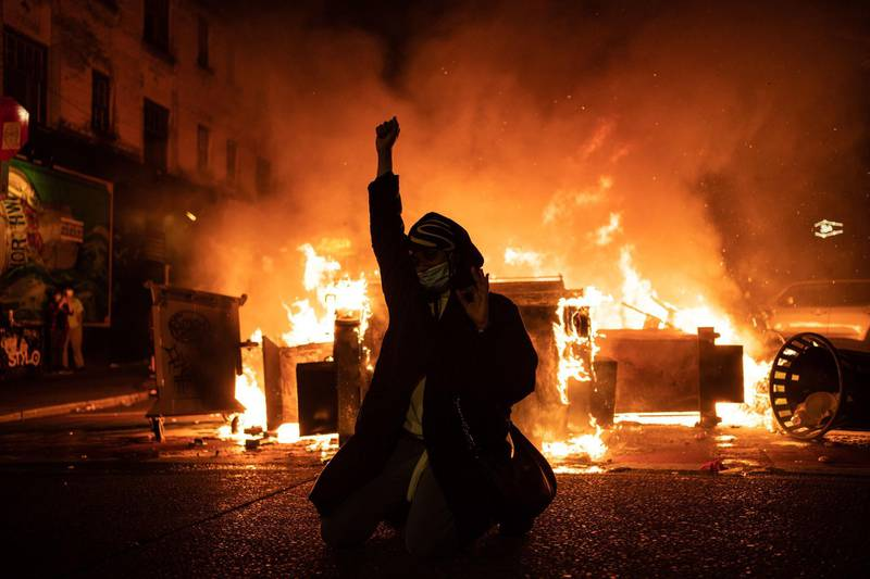 SEATTLE, WA - JUNE 08: A demonstrator raises their fist as a fire burns in the street after clashes with law enforcement near the Seattle Police Departments East Precinct shortly after midnight on June 8, 2020 in Seattle, Washington. Earlier in the evening, a suspect drove into the crowd of protesters and shot one person, which happened after a day of peaceful protests across the city. Later, police and protestors clashed violently during ongoing Black Lives Matter demonstrations following the death of George Floyd.   David Ryder/Getty Images/AFP == FOR NEWSPAPERS, INTERNET, TELCOS & TELEVISION USE ONLY ==