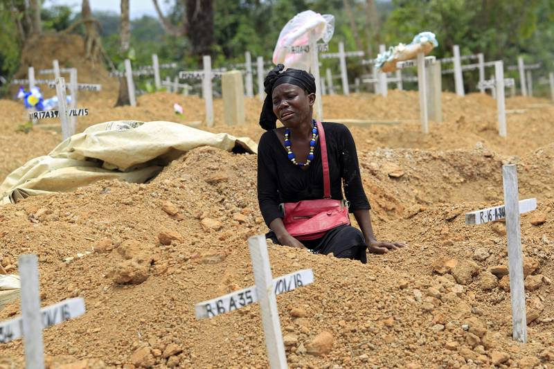 epa05203587 A woman mourns at her father's grave at Disco Hill Safe Burial Site, in Margibi County, Liberia, 09 March 2016. Decoration Day or Memorial Day is observed on the second Wednesday of March in Liberia, 09 March 2016 for the current year, to honor and remember the dead.  EPA/AHMED JALLANZO