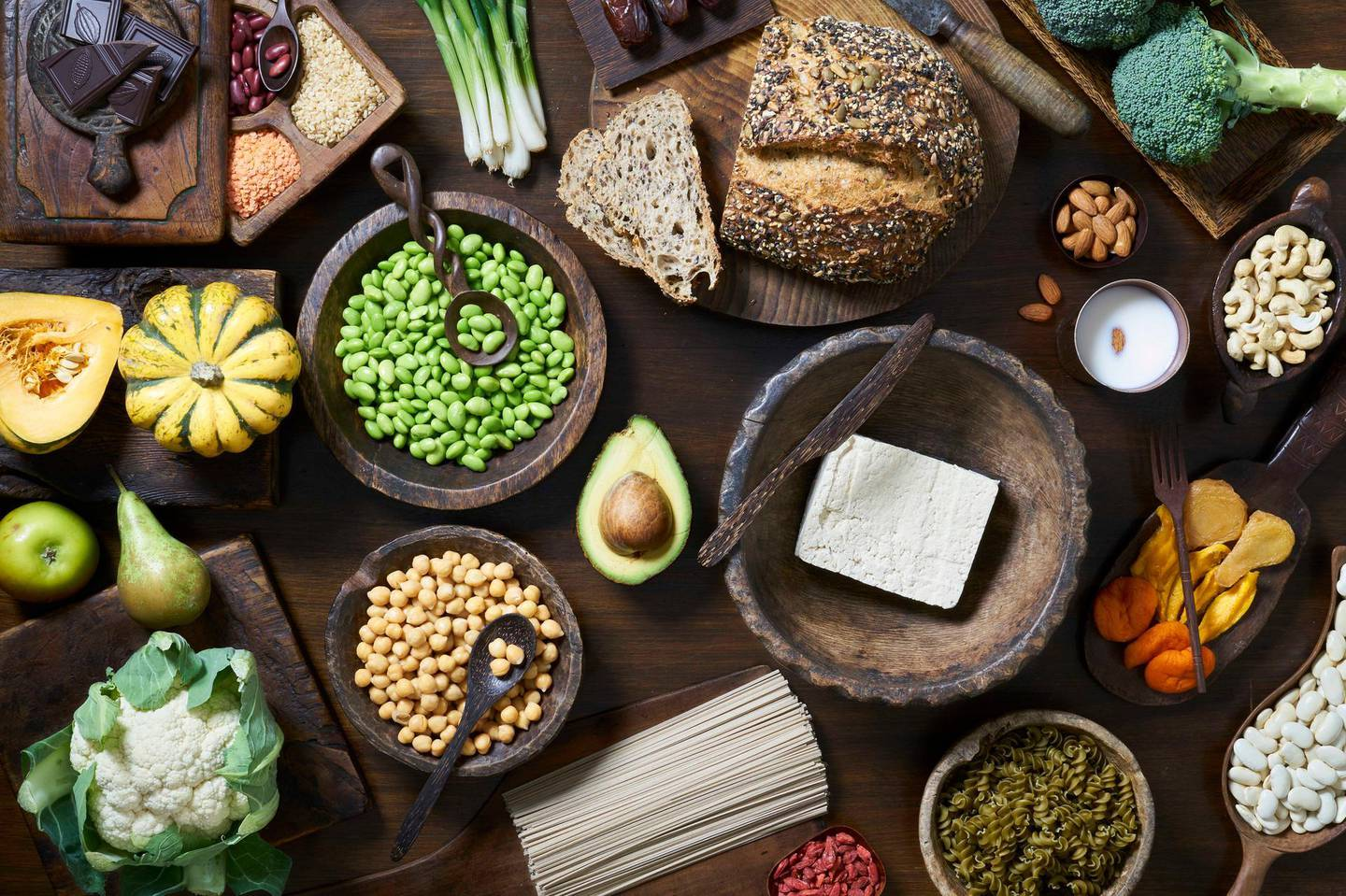Overhead shot of healthy vegan food including fruit vegetables tofu and beans. Getty Images