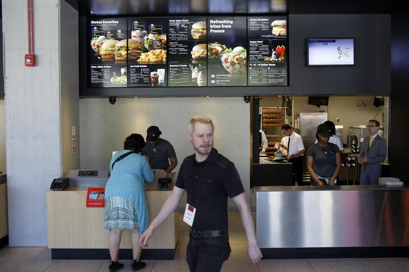 An employee takes a customer's order at the restaurant inside the new McDonald's Corp. headquarters in Chicago, Illinois, U.S., on Monday, June 4, 2018. McDonald's CEO Steve Easterbrook said that the headquarters move to Chicago will help draw talent to the company. Photographer: Joshua Lott/Bloomberg