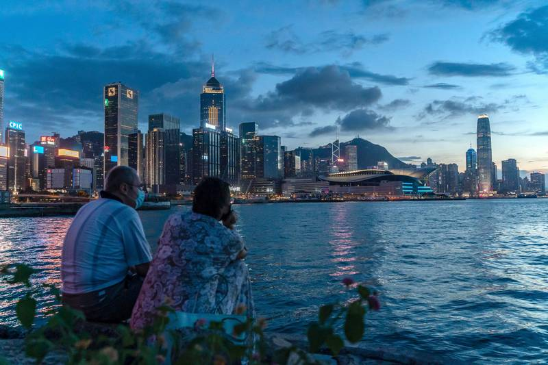 HONG KONG, CHINA - JULY 30: A couple enjoy their moment at a typhoon shelter during sunset in front of Hong Kong skyline on July 30, 2020 in Hong Kong, China. Hong Kong have recorded the highest daily tally of Covid-19 with 149 confirmed cases. (Photo by Anthony Kwan/Getty Images)