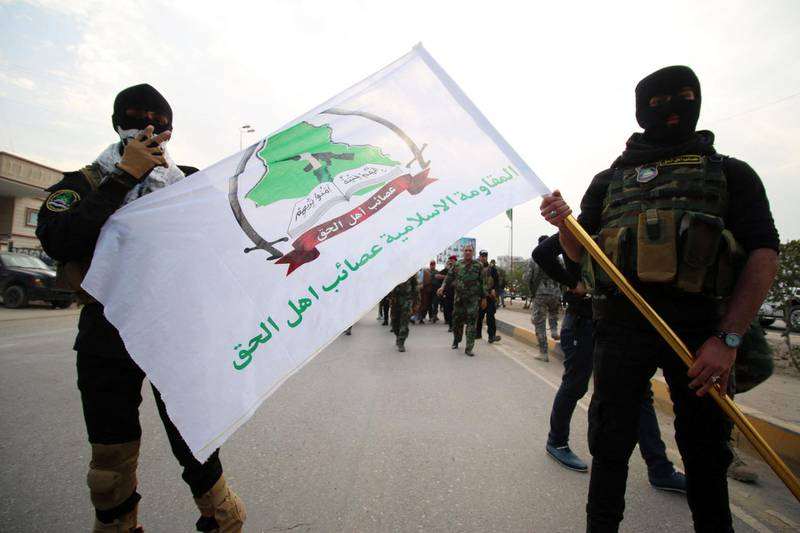 Iraqi Shiite members of the Asaib Ahl al-Haq group (The League of the Righteous) units gather in the southern city of Basra on December 12, 2015, to demand the withdrawal of Turkish forces from Iraq. Iraq says Turkey deployed troops and tanks to a base in the country's north last week without its permission, sparking a diplomatic uproar between Baghdad and Ankara. (Photo by HAIDAR MOHAMMED ALI / AFP)