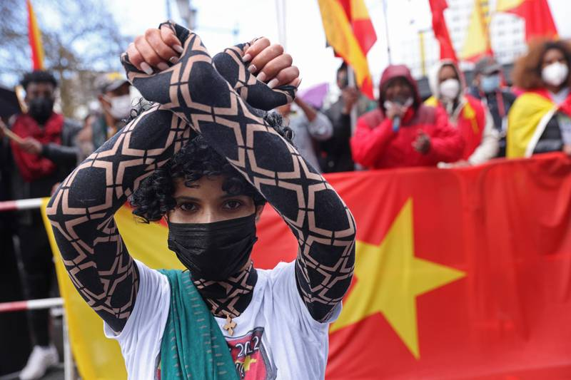 BERLIN, GERMANY - MAY 07: A protester kneels during a demonstration against Ethiopia's war against Tigray regional forces near the Chinese Embassy on May 07, 2021 in Berlin, Germany. The protesters were also demanding the Chinese government stop supporting the Ethiopian government. The Tigray War began in 2020 and is ongoing. (Photo by Sean Gallup/Getty Images)