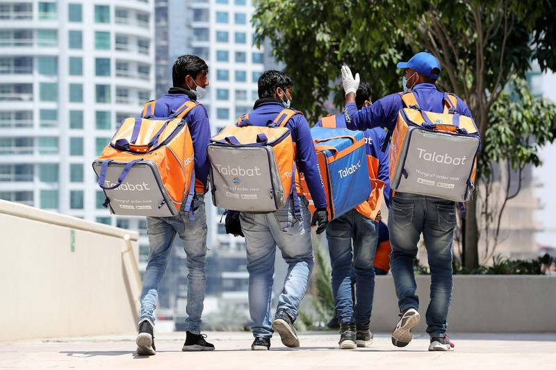 DUBAI, UNITED ARAB EMIRATES , April 17– 2020 :- Talabat delivery guys going to collect their orders in Dubai Marina in Dubai. Dubai is conducting 24 hours sterilisation programme across all areas and communities in the Emirate and told residents to stay at home. UAE government told residents to wear face mask and gloves all the times outside the home whether they are showing symptoms of Covid-19 or not.  (Pawan Singh / The National) For News/Online/Instagram