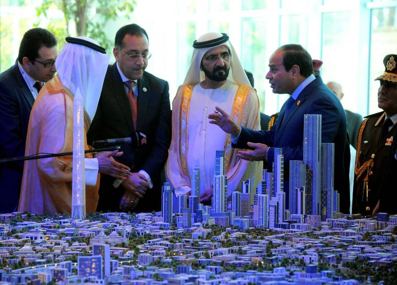 A handout picture made available on March 14, 2015 by the Egyptian presidency shows Egyptian President Abdel Fattah al-Sisi (R) and Prime Minister of the United Arab Emirates (UAE) and ruler of Dubai Sheikh Mohammed bin Rashid al-Maktoum (C) listening to Egyptian investment minister Ashraf Salman (3rdR) as they look at a scale model of the new Egyptian capital Cairo displayed at the congress hall in the Red Sea resort of Sharm el-Sheikh. (Photo by MOHAMED SAMAAHA / EGYPTIAN PRESIDENCY / AFP)