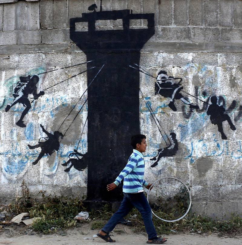 epa04699335 A Palestinian boy walks past a graffiti mural of children using an Israeli army watch tower as a swing ride, presumably painted by British street artist Banksy, on the wall of destroyed homes in Beit hanun town in the northern Gaza Strip, 10 April 2015.  EPA/MOHAMMED SABER *** Local Caption *** 51882350