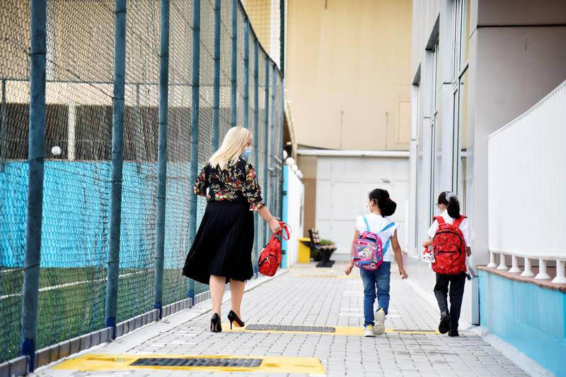 A facility member assists students to their classrooms at the Al-Mizhar American Academy after the government re-opens schools in the wake of the Covid-19 pandemic, in Dubai, UAE, Sunday, Aug. 30, 2020. (Photos by Shruti Jain - The National)
