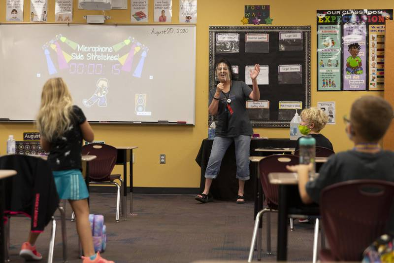 A teacher wears a face shield during a lesson at an elementary school in Surprise, Arizona, U.S., on Thursday, Aug. 20, 2020. Arizona's downward trend of coronavirus cases means parts of the state could meet all three metrics the state's health and education departments set for at least a partial reopening of schools by Labor Day. Schools are not bound by the rules, and some have reopened already, the Associated Press reports. Photographer: Cheney Orr/Bloomberg