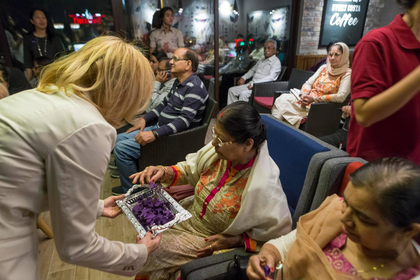 DUBAI, UNITED ARAB EMIRATES, 07 MARCH 2017. A group of elderly people from the Golden Age group met up at the new Costa Cafe on Jumeirah Beach Road as part of a new initiative titled Alzheimer's Café. Alzheimer's Cafe plan to host monthly meetings focusing on Alzheimer's support and brain health matters. Birgit Ertl, Founder of the International Curriculum for Language and Creative Arts hands out purple Alzheimer's ribbons to the participants at the meeting. (Photo: Antonie Robertson/The National) ID: 52004. Journalist: Amna Shahid. Section: National. *** Local Caption ***  AR_0703_Alzheimers_Support-01.JPG