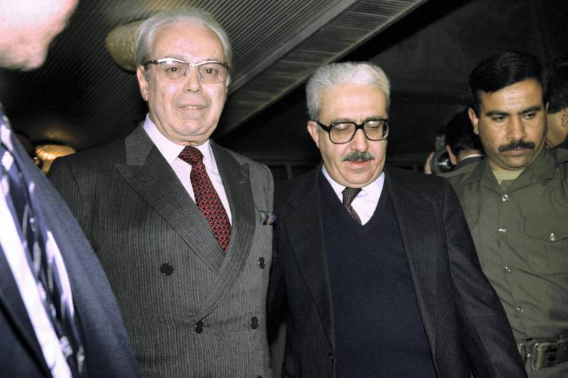 UN Secretary General Javier Perez de Cuellar (L) is accompanied by Iraqi Foreign Minister Tareq Aziz upon his arrival on Januray 12, 1991 to hold last chance peace talks with Iraqi President Saddam Hussein. (Photo by Gerard FOUET / AFP)