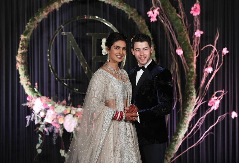 epa07208512 Newlyweds, Bollywood actress Priyanka Chopra (L) and US musician Nick Jonas (R) pose for photographs during a reception in New Delhi, India, 04 December 2018. According to media reports, the couple hosted wedding celebrations in Jodphur on 01 and 02 December.  EPA/RAJAT GUPTA