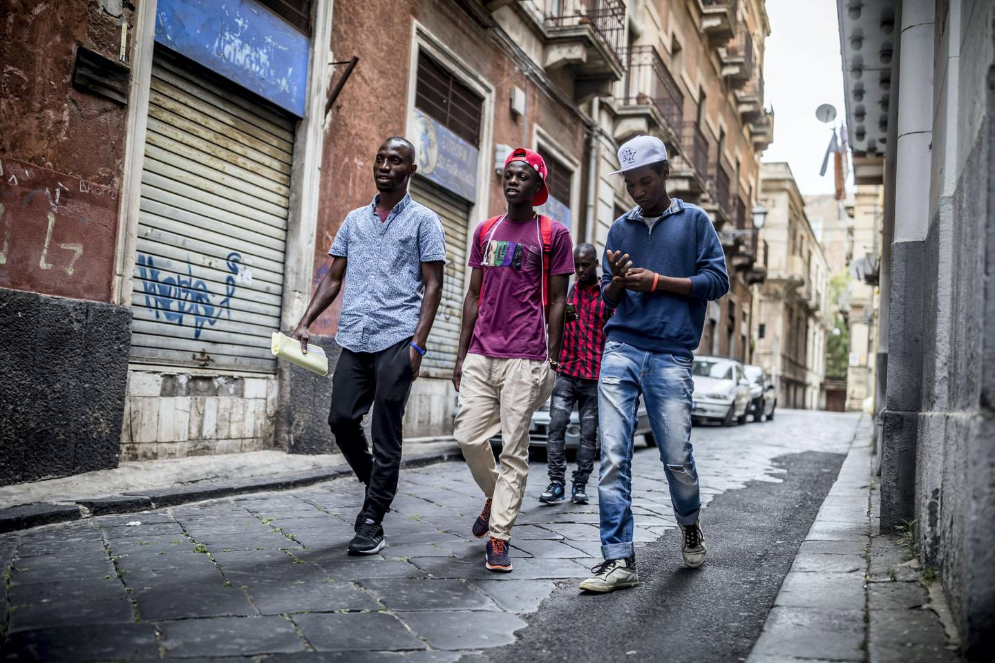 The refugees Mikailou Diallo (L-R), Landing Solly Ameidou Sidy Iraore and Asowe Abdoulie walk after a visit at the community center through Catania in Sicily, Italy, 25 May 2017. Social workers take care of the refugees at the community center. Refugees and other migrants can feel safe and get counselling. The heads of the G7 states meet in Sicily from 26 May until 27 May 2017. Photo by: Michael Kappeler/picture-alliance/dpa/AP Images