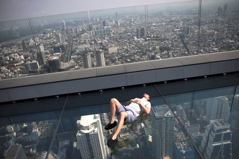 BANGKOK, THAILAND - MARCH 20:  A man lies on the glass tray at MahaNakhon Skywalk atop King Power MahaNakhon on March 20, 2019 in Bangkok, Thailand. The tower opened in November 2018 and features Thailand's tallest observatory and rooftop bar. (Photo by Brent Lewin/Getty Images)