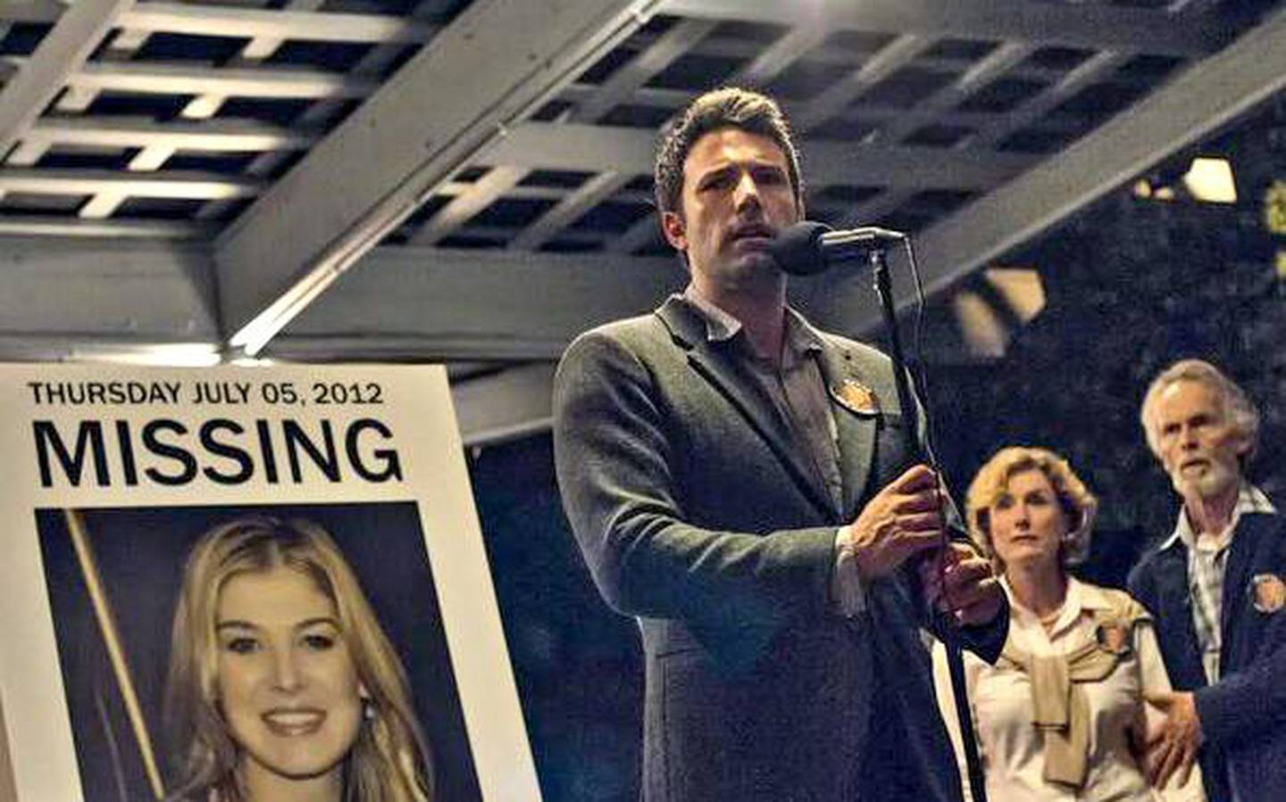Ben Affleck, and Rosamund Pike (on the poster) in the first photo released by 20th Century Fox for the much anticipated movie, Gone Girl. Dec.29, 2013. At left are Lisa Banes and David Clennon. CREDIT: Courtesy 20th Century Fox *** Local Caption ***  blog.Gone.Girl.jpg