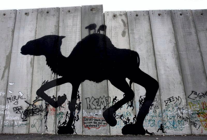 epa01191036 Illusive British graffiti artist named Banksy has painted new works in the West Bank town of Bethlehem and this work of a camel with human figures climbing up and down its legs on 04 December 2007 could be one of his new works. It is executed on a huge cement wall, but not the controversial 'separation barrier,' that protects an Israeli military base inside, on the outskirts of Bethlehem. The works are not signed. These new works are being dubbed 'West Banksy,' and some are painted on the controversial Israeli 'separation barrier,' or wall, that surrounds Bethlehem and cuts its residents off from nearby Jerusalem.  EPA/JIM HOLLANDER *** Local Caption *** 01191036