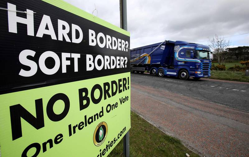 """A lorry passes a poster by calling for """"No Border"""" between Ireland and Northern Ireland, in a post Brexit United the anti-brexit campaign group """"Border communities against Brexit"""" in Jonesborough, Northern Ireland on March 25, 2019, as it crosses the border between Ireland and Northern Ireland.  Keeping the Irish border free-flowing has proved to be the toughest issue to resolve in negotiating Britain's exit from the European Union. The Brexit deal between London and Brussels -- overwhelmingly rejected last week by British MPs -- contains a so-called backstop provision ensuring that if all else fails, the border will remain open. / AFP / PAUL FAITH"""