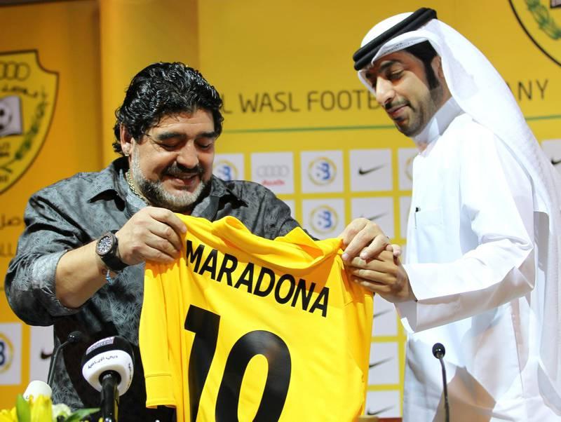 Argentine football legend Diego Maradona (L) looks at his new shirt with Marwan Bin Bayat, chairman of the Emirati al-Wasl Football Company, during a press conference in Dubai, on September 11, 2011. AFP PHOTO/Karim SAHIB (Photo by KARIM SAHIB / AFP)