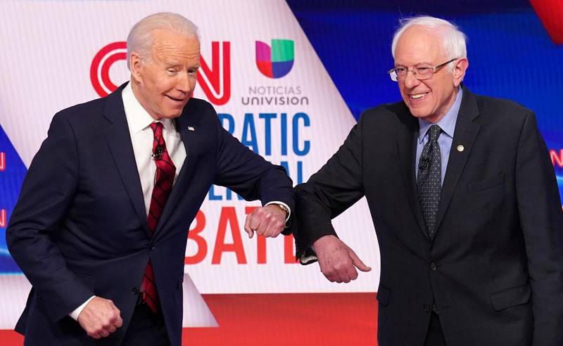 Democratic U.S. presidential candidates former Vice President Joe Biden and Senator Bernie Sanders do an elbow bump in place of a handshake as they greet other before the start of the 11th Democratic candidates debate of the 2020 U.S. presidential campaign, held in CNN's Washington studios without an audience because of the global coronavirus pandemic, in Washington, U.S. March 15, 2020. REUTERS/Kevin Lamarque