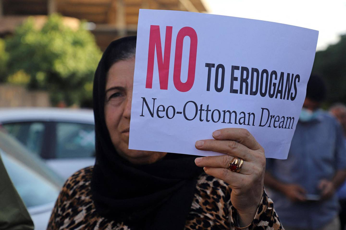"""A woman lifts a placard as Iraqi Kurds demonstrate  in the northeastern city of Sulaimaniyah on June 5, 2021, protesting a Turkish offensive in northern Iraq. Three civilians were killed in a Turkish drone attack on a refugee camp in northern Iraq in an area which Turkish President Recep Tayyip Erdogan recently threatened to """"clean up"""". / AFP / Shwan MOHAMMED"""
