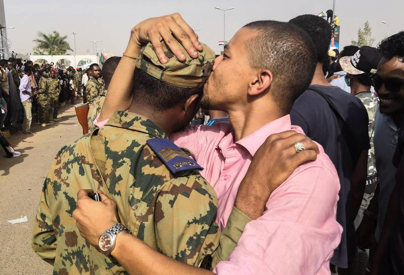 """A Sudanese anti-regime protester kisses a soldier on the head during protests on April 11, 2019 in the area around the army headquarters in Sudan's capital Khartoum. - The Sudanese army is planning to make """"an important announcement"""", state media said today, after months of protests demanding the resignation of longtime leader President Omar al-Bashir. Thousands of Khartoum residents chanted """"the regime has fallen"""" as they flooded the area around the military headquarters, where protesters have held an unprecedented sit-in now in its sixth day. (Photo by - / AFP)"""