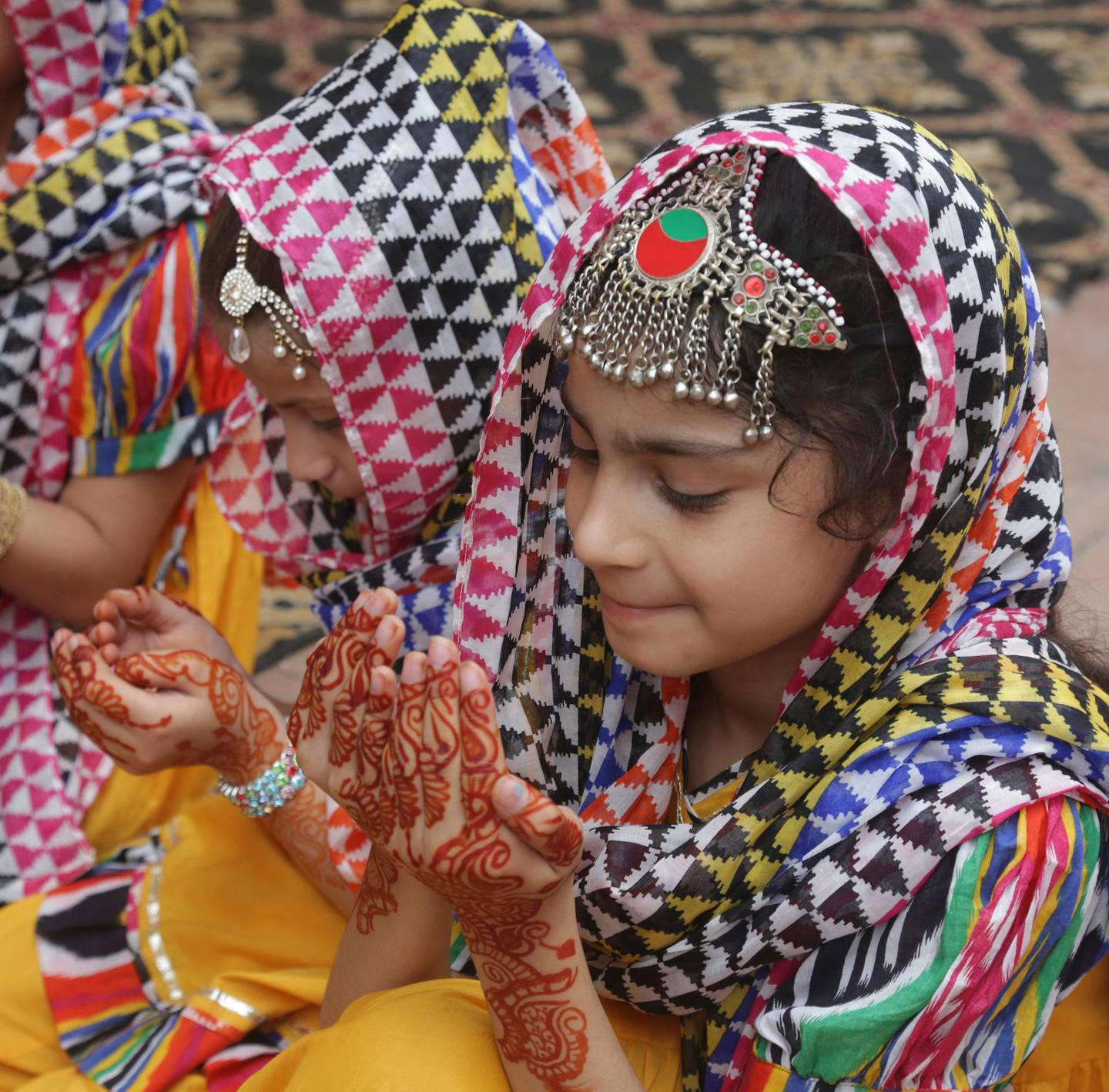 Pakistani girls, with their hands decorated with henna, pray during the Eid al-Adha holiday, in Lahore Pakistan, Wednesday, Aug. 22, 2018. Muslims around the world celebrate Eid al-Adha, or the Feast of the Sacrifice, that marks the willingness of the Prophet Ibrahim (Abraham to Christians and Jews) to sacrifice his son. During the holiday, which in most places lasts four days, Muslims slaughter sheep or cattle, distribute part of the meat to the poor and eat the rest. (AP Photo/K.M. Chaudary)