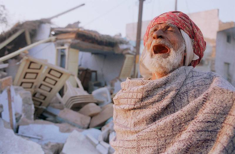 384982 03: A Muslim man weeps in front of his destroyed house January 29, 2001 in Bhuj, India. Bhuj and the surrounding villages in the western Indian state of Gujarat lay at the epicenter of Friday''s earthquake, which registered 7.9 on the Richter scale. Few structures remain standing amidst the rubble. (Photo by Alyssa Banta/Newsmakers)
