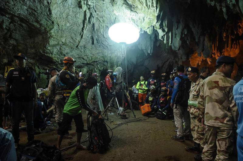 Thai rescue personnel are set up at the entrance of Tham Luang cave under floodlights to conduct operations to find the missing members of the children's football team along with their coach at the cave in Khun Nam Nang Non Forest Park in Chiang Rai province on June 26, 2018.  / AFP / LILLIAN SUWANRUMPHA