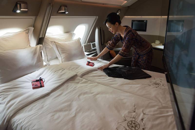 An air stewardess arranges bedsheets of a double bed in a suite of Singapore Airlines' new Airbus A380 during a tour of the plane at Changi Airport in Singapore on December 14, 2017. - The research, design, development and installation of the new products on 19 Singapore Airlines A380 planes represent an investment of about 850 million USD, SIA said. (Photo by TOH Ting Wei / AFP) / ���The erroneous mention[s] appearing in the metadata of this photo by TOH Ting Wei has been modified in AFP systems in the following manner: Correcting the second sentence. Please immediately remove the erroneous mention[s] from all your online services and delete it (them) from your servers. If you have been authorized by AFP to distribute it (them) to third parties, please ensure that the same actions are carried out by them. Failure to promptly comply with these instructions will entail liability on your part for any continued or post notification usage. Therefore we thank you very much for all your attention and prompt action. We are sorry for the inconvenience this notification may cause and remain at your disposal for any further information you may require.���