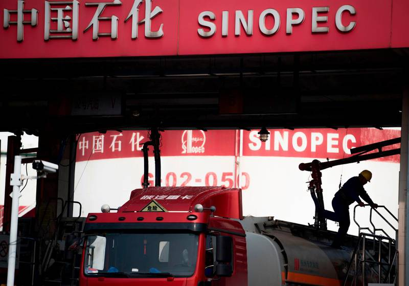 This picture taken on March 22, 2018 shows a man working in a filling station of Sinopec, China Petroleum and Chemical Corporation, in Shanghai.  China launched yuan-denominated oil futures contracts on March 26, marking the first time foreign investors will have access to Chinese commodity futures as the world's top crude importer seeks greater influence over global prices. / AFP PHOTO / Johannes EISELE