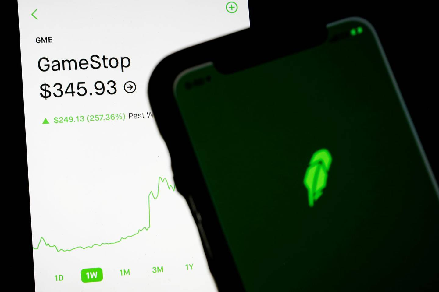 FILE PHOTO: Trading information for GameStop is displayed on the Robinhood App as another screen displays the Robinhood logo in this photo illustration January 29, 2021. REUTERS/Brendan McDermid/Illustration/File Photo