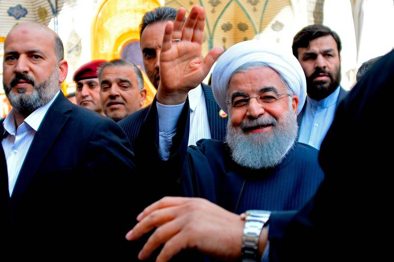 """Iranian President Hassan Rouhani (C) visits in the Iraqi central city of Najaf on March 13, 2019. Iran's President Hassan Rouhani hit back on March 11 against pressure from the """"aggressor"""" United States on Iraq to limit ties with its neighbour, during his first official visit to Baghdad. Shiite-majority Iraq is walking a fine line to maintain good relations with its key partners Iran and the United States which themselves are arch-foes. / AFP / Haidar HAMDANI"""
