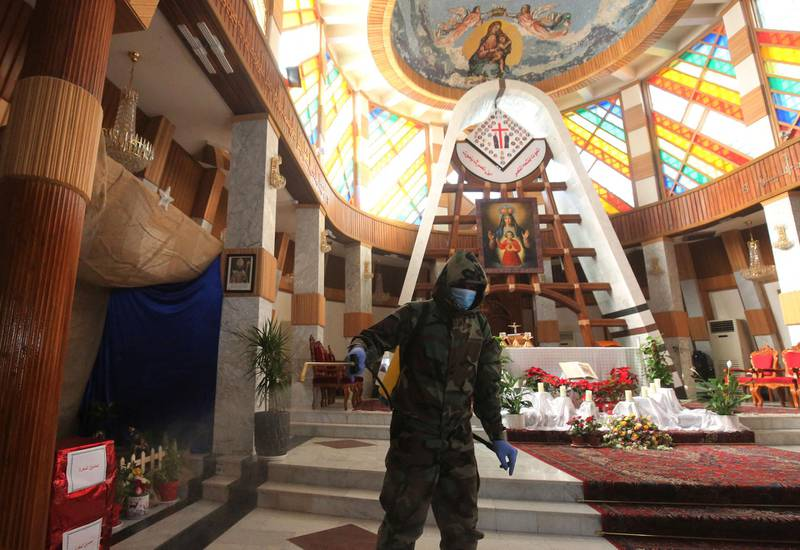 Iraqi members of a civil defence team disinfect the Our Lady of Salvation church in central Baghdad on December 30, 2020 amid measures to contain the spread of the Covid-19 coronavirus. (Photo by AHMAD AL-RUBAYE / AFP)