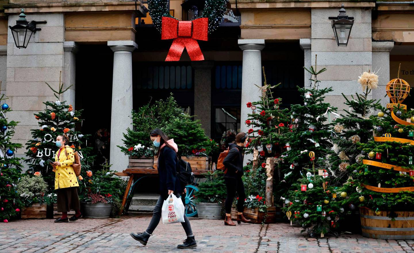 Pedestrians wearing face masks or coverings due to the COVID-19 pandemic, walk past Christmas trees in Covent Garden in central London on November 17, 2020. Britain has been the worst-hit nation in Europe recording more than 50,000 coronavirus deaths from some 1.2 million positive cases. / AFP / Tolga Akmen